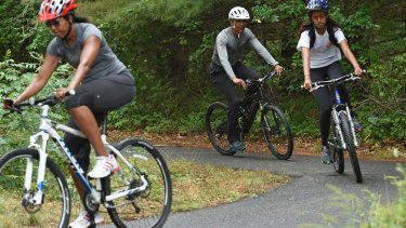 From left: Michelle Obama, Barack Obama and their eldest daughter Malia ride their bikes while on holidays in Martha's Vineyard during his presidency.