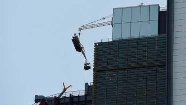 The damaged crane hangs from the 51st floor of the highest tower at Barangaroo in the Sydney CBD.