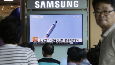 People watch a TV news program showing file footage of North Korea's ballistic missile that the North claimed to have launched from underwater, at Seoul Railway station in Seoul.
