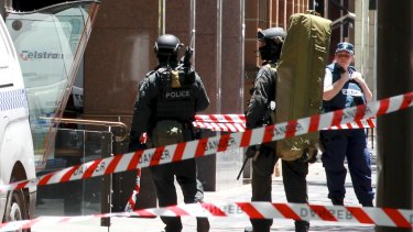 Police snipers enter Martin Place from Macquarie Street as the siege unfolded.