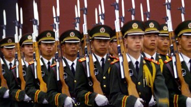Chinese soldiers with fixed bayonets attend the flag-raising ritual at dawn in Tiananmen Square.
