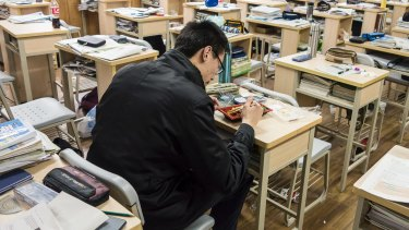 A student eats his lunch while sitting in his classroom at Shanghai High School in Shanghai, China.
