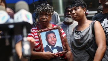 July 2015: Gwen Carr, mother of Eric Garner, who died after a police officer used a choke hold on him in 2014, holds a photo of him at a news conference in New York.