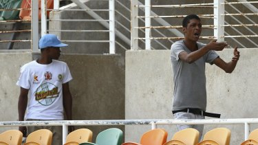 Locals argue over match tickets during an Australian nets session at Sabina Park.