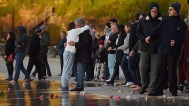 Parents of Justine Damond, Maryan Heffernan (centre left, white top, jeans) and John Ruszczyk (centre right, black coat, glasses) embrace at the Freshwater Beach water's edge during a vigil for their daughter.
