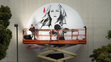 Street artist Vexta paints her image at the back of the St Kilda police station.