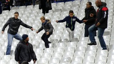 Soccer fans leave the Stade de France stadium after an international friendly soccer match in Saint Denis, outside Paris. An explosion occurred outside the stadium. Several dozen people were killed in a series of unprecedented attacks around Paris on Friday, French President Francois Hollande said, announcing that he was closing the country's borders and declaring a state of emergency.