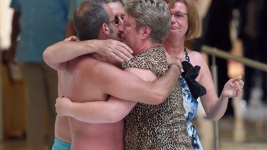 Tourists console each other following the shooting attack.