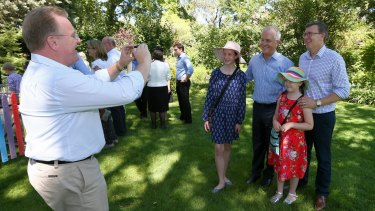 Liberal MP Bruce Billson helps Alan Tudge take of photo of his family together with Prime Minister Malcolm Turnbull.