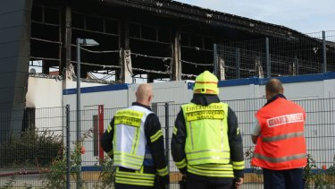 Emergency services workers outside a sports hall in Nauen on Tuesday. Intended to house refugees and migrants applying for asylum in Germany, the hall was burned.