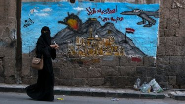 A woman passes a mural depicting airstrikes in Sanaa, Yemen.