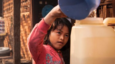 Htoi Nu Mai, 9, fills up a water container outside her family's shelter at the Phan Khar Kone IDP camp in Bhamo city, Kachin State, Myanmar.