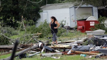 Jennifer Bryant looks over the debris where her family business once stood.