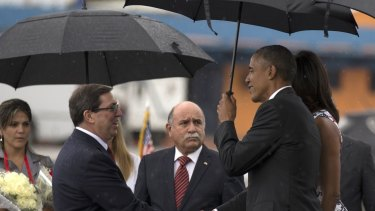 President Barack Obama, right, shakes hands with Cuba's Foreign Minister Bruno Rodriguez as first lady Michelle Obama stands behind, right, at the airport in Havana, Cuba.