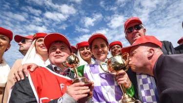 Stevie Payne, left, with sister Michelle, trainer Darren Weir and one of the owners kissing the cup.