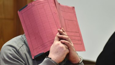 Former nurse Niels Hoegel, accused of multiple murder and attempted murder of patients, covering his face with a file at the district court in Oldenburg, Germany in February.