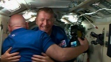 British Flight Engineer Tim Peake of the European Space Agency, centre, hugs Scott Kelly as Peake, Tim Kopra of NASA and cosmonaut Yuri Malenchenko board the International Space Station.