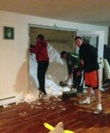 Mark Hazard, his son Jason and Bryan Juda shovel out the snow from their Cheektowaga, New York, home.