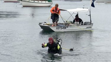 Underwater walker Rod Moore emerges from Rushcutters Bay at the end of his trek across Sydney Harbour.