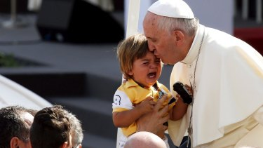 Pope Francis kisses a child as he arrives to lead a mass in Turin, Italy, during a two-day pastoral visit last week.