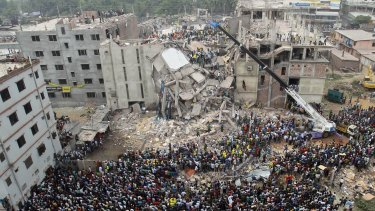 Bangladeshi people gather as rescuers look for survivors and victims at the site of the Rana Plaza collapse in April 2013.
