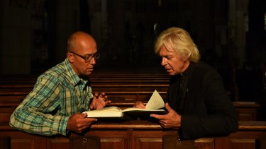 Thomas Schansman (left), the father of MH17 victim Quinn Schansman, looks through the condolence book with Pastor Jules Dresme at St Vitus Church in Hilversum, the Netherlands.