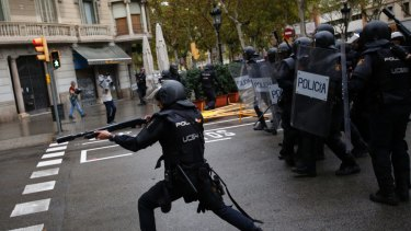 A Spanish riot police officer shoots rubber bullet at people trying to reach a voting site at a school assigned to be a polling station by the Catalan government in Barcelona.