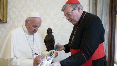Perhaps it should have been a broom. Pope Francis signs a cricket bat he received from Cardinal George Pell at the Vatican.