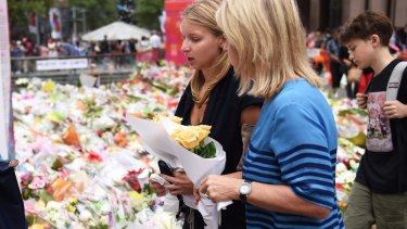 Madeleine Pulver, victim of the collar bomb incident, fights back tears before placing flowers near the scene of the Martin Place siege with her mother on Thursday.