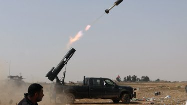 Iraqi security forces launch a rocket against Islamic State extremist positions during clashes in Tikrit on March 30.