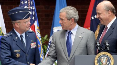 US president George W. Bush shakes hands with Air Force General Michael Hayden, director of the CIA at the time of the Mughniyah assassination, in 2005. John Negroponte, then Director of National Intelligence, looks on.