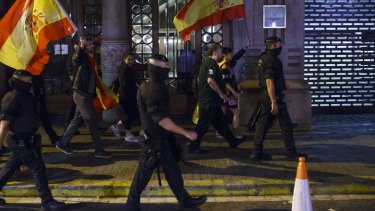 People hold Spanish national flags while being escorted by Mossos d'Esquadra, the Catalan police force.