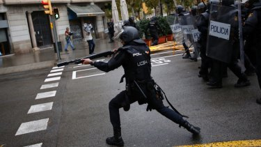 Spanish riot police fire rubber bullets trying to stop people reaching a voting site.