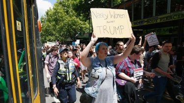 Protesters against Donald Trump walk along Swanston Street stopping trams.