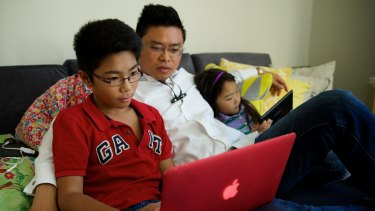 Joss,12, and Darcy Nguyen, 7, often do school research online with their father Tung Nguyen on their tablet or laptop using the NBN.