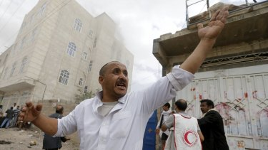 Red Crescent workers and civilians in the streets after an air strike in the Yemeni capital.