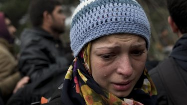 A woman cries as refugees and migrants protest in front of the border gate that separates Greece from Macedonia near the northern Greek village of Idomeni on Monday.