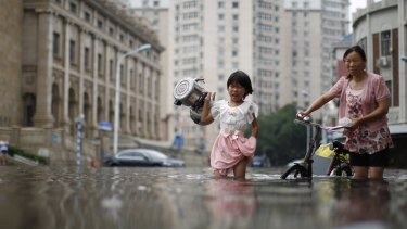 A child carries kettles through a flooded street with a woman in Tianjin, China, in July.