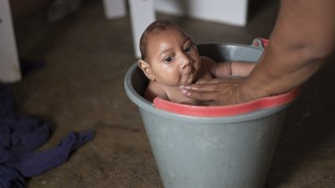 Solange Ferreira bathes her son Jose Wesley in a bucket at their house in Poco Fundo, Pernambuco, Brazil. Ferreira says her son enjoys being in the water, she places him in the bucket several times a day to calm him.