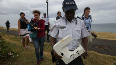 National Police Brigadier Gisele Cadar carries the plastic beach debris away from St Denis beach, Reunion Island on Tuesday.