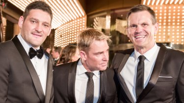 Shane Warne, flanked by Brendan Fevola and Paul Harragon, shies away from Fairfax Media's camera at the Logie Awards.
