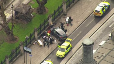 In this image taken from video, police officers gather around a car adjacent to Houses of Parliament in London.