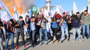 Participants in the peace rally react at the moment of the first explosion on Saturday.