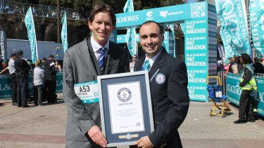 Matthew Whitaker with his Guinness World Record certificate after completing the Sydney Running Festival marathon wearing a suit.