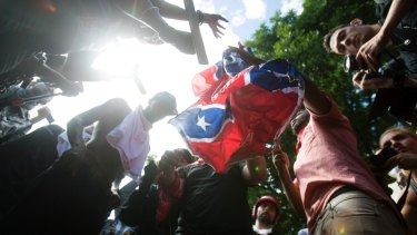 Counter-protesters tear a Confederate flag during the white nationalist rally, on Saturday.