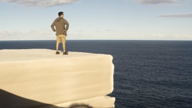 A man stands on Wedding Cake Rock.