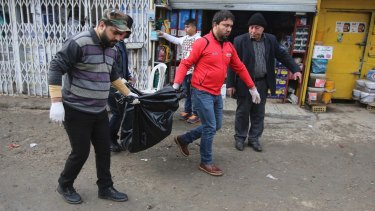 Men carry the body of a person killed in the blast in Baghdad.