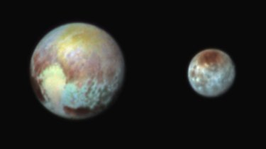 A combination image released by NASA on July 13 shows Pluto, left, and its moon, Charon, with differences in surface material and features depicted in exaggerated colours made by using different filters on a camera aboard the New Horizons spacecraft.