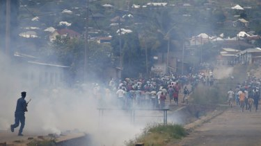 Protesters flee as police fire tear gas during a protest in Bujumbura on Tuesday.
