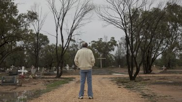 Ormie Molyneaux waits at a cemetery in Lightning Ridge.
